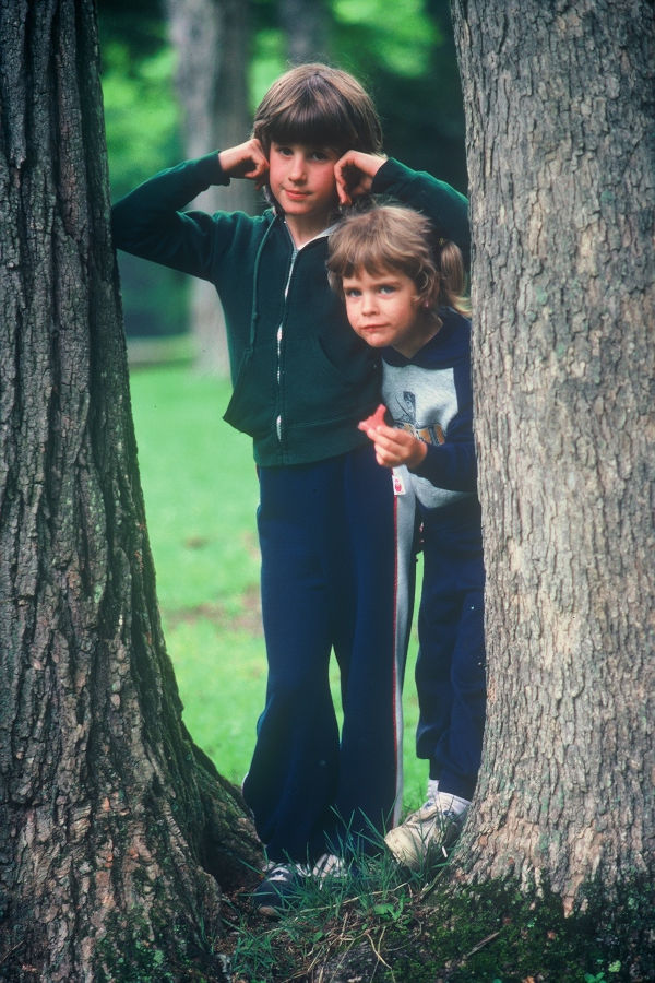 David Bott's daughters, Rachelle (Bott) Beckner and Sara Bott peer between the pine trees at Cabin 20 near the swimming pool. | 📸: Leonard Bott