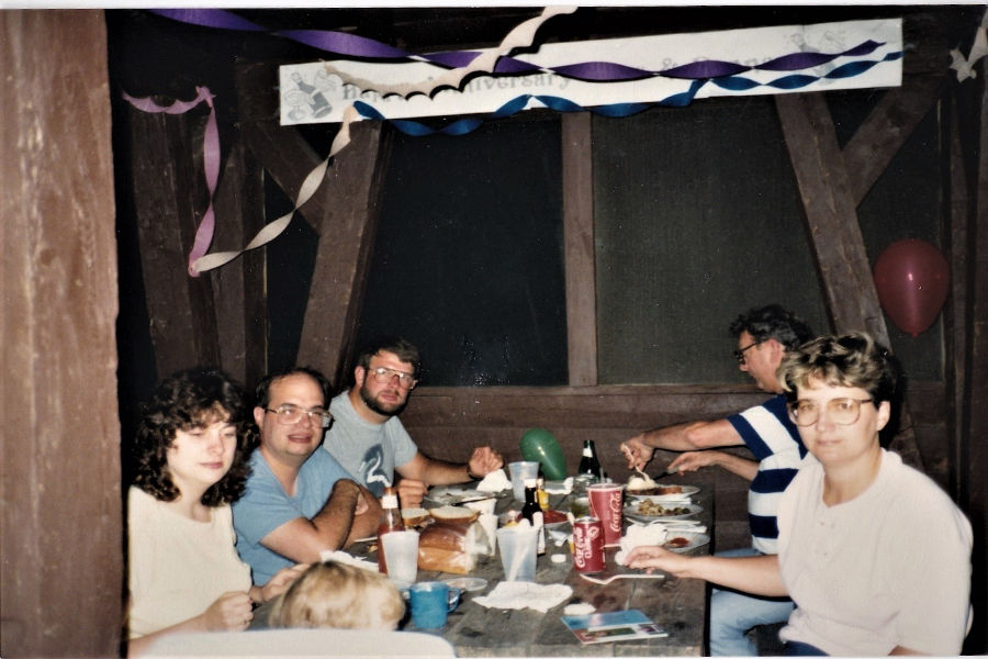 We are celebrating my parents' wedding anniversary on August 19, 1988 in Cabin 14 at Watoga. From L-R, foreground to background: Joanna Joseph Reynolds, my cousin, in highchair; Aunt Barbara Bott Joseph; Uncle Bob Joseph, my dad, David Bott, across from him Grandpa Bott (Leonard S. Bott); and my mom, Donna Bott. 📸: Rachelle Bott Beckner.Rachelle Bott Beckner.