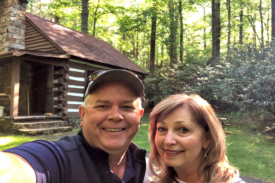 All smiles are Ken and Judy Caplinger as they pose for a selfie making memories t Watoga State Park, Cabin No. 34, also known as the Honeymoon Cabin. The log cabin is in the background surround by a lush forest and mountain laurel that is common through West Virginia's largest state park.
