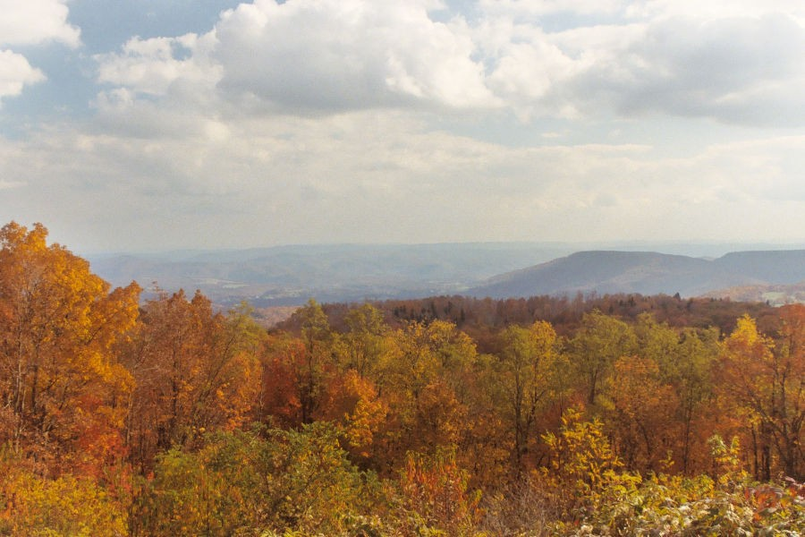 Hues of orange red and yellow highlight the foreground of TM Cheek Memorial Overlook where you can see Kennison Mountain and the Greenbrier River Valley in the distance. Always worth a photo no matter the season is the overlook at T.M. Cheek Memorial. Photo by Stanley©.