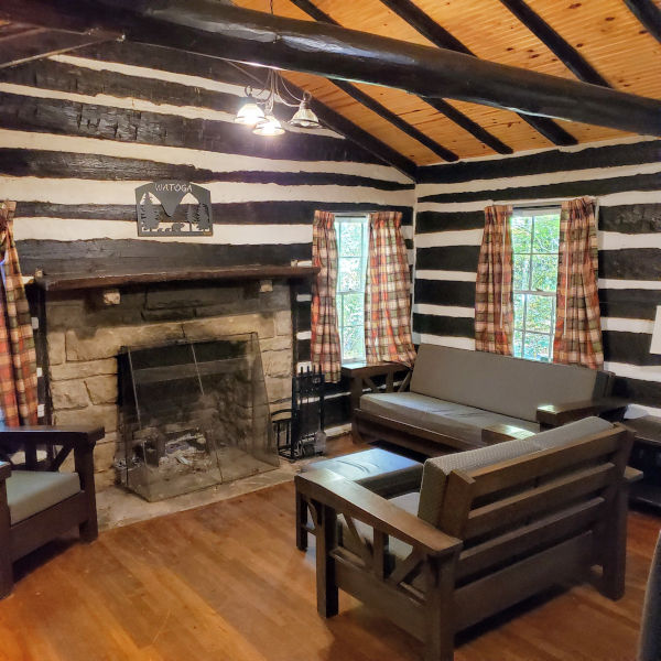 Interior of a Legacy Cabin (Cabin No. 11) highlights new furniture and interior upgrades. A fireplace takes center state as does the wood work and hewn logs from the 1930s.Photo by John Dean.