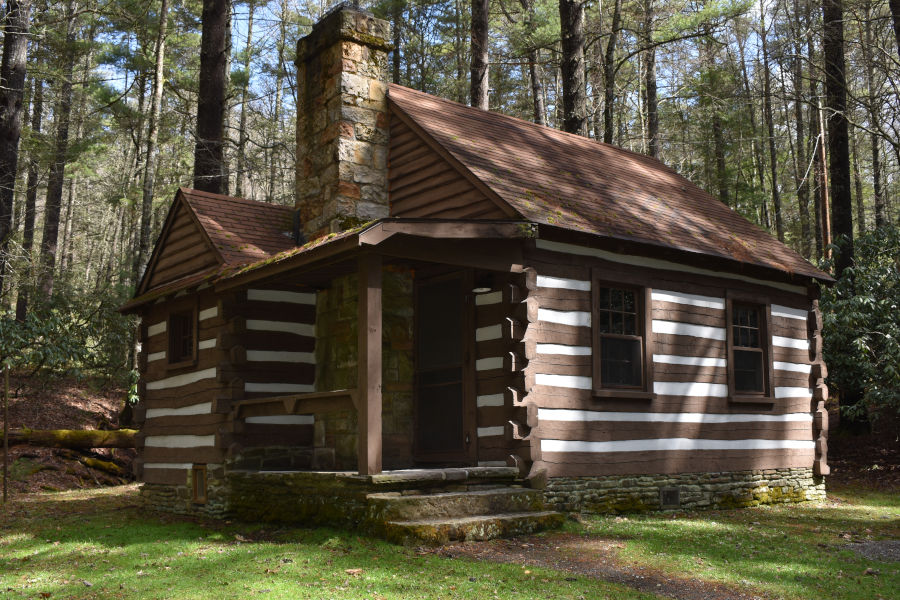 "A log cabin build by the Civilian Conservation Corp in the early 1930s is nestled neatly again a backdrop of tall tress as spring and green begins to emerge in 2021. Cabin 34 - the ""Honeymoon Cabin,"" is a Top 10 choice for newlyweds. 📸: John C. Dean"
